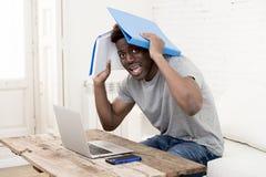 Uomo afroamericano che si siede a casa salone che lavora con il computer portatile ed il lavoro di ufficio Immagine Stock Libera da Diritti