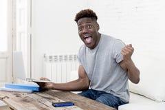 Uomo afroamericano che si siede a casa salone che lavora con il computer portatile ed il lavoro di ufficio Immagini Stock
