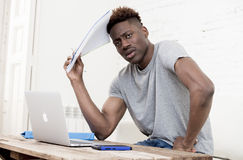 Uomo afroamericano che si siede a casa salone che lavora con il computer portatile ed il lavoro di ufficio Fotografia Stock Libera da Diritti