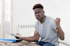 Uomo afroamericano che si siede a casa salone che lavora con il computer portatile ed il lavoro di ufficio Immagini Stock Libere da Diritti
