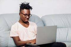 Uomo afroamericano che si siede con il computer portatile sul sofà Immagini Stock