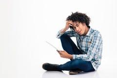 Uomo afroamericano che si siede sul pavimento con il computer portatile Fotografia Stock Libera da Diritti