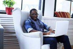 Uomo afroamericano che si siede sulla sedia immagini stock libere da diritti