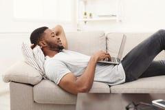 Uomo afroamericano con il computer portatile all'interno Immagini Stock Libere da Diritti