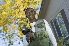 Uomo afroamericano con le canne da pesca Immagine Stock