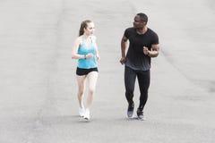 Uomo afroamericano delle giovani coppie felici e donna europea che corrono insieme Una coppia amorosa è funzionata, impegnato neg fotografia stock libera da diritti