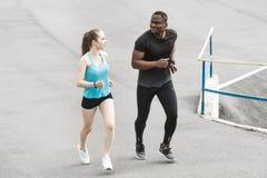 Uomo afroamericano delle giovani coppie felici e donna europea che corrono insieme Una coppia amorosa è funzionata, impegnato neg fotografia stock