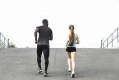 Uomo afroamericano delle giovani coppie felici e donna europea che corrono insieme Una coppia amorosa è funzionata, impegnato neg fotografie stock libere da diritti