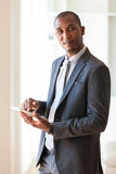 Uomo afroamericano di affari che per mezzo di una compressa tattile - peop nero Fotografia Stock Libera da Diritti