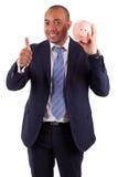 Uomo afroamericano di affari che tiene un porcellino salvadanaio che fa i pollici Fotografie Stock Libere da Diritti