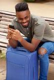 Uomo afroamericano di Oung che si siede con il telefono cellulare e la valigia Fotografia Stock Libera da Diritti