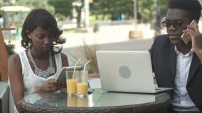Uomo afroamericano e donna di affari che lavorano insieme in caffè moderno, avendo telefonate, facendo uso del computer portatile stock footage