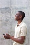 Uomo afroamericano felice che cammina con il telefono cellulare Fotografia Stock Libera da Diritti