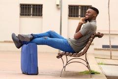 Uomo afroamericano felice che si siede fuori con la valigia e che parla sul telefono cellulare Fotografia Stock