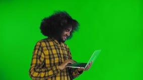 Uomo afroamericano felice facendo uso del computer portatile, sorridendo ed andare via sullo schermo verde o sul fondo chiave di  archivi video
