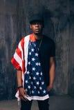Uomo afroamericano fiero con la bandiera americana Immagine Stock