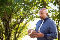 Uomo afroamericano maturo che tiene un calcio fotografie stock