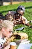 Uomo afroamericano in occhiali da sole che esaminano i compagni di classe che studiano con i libri su erba Immagine Stock