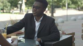 Uomo afroamericano piacevole che ha telefonata durante la pausa di lavoro con il suo calleague stock footage