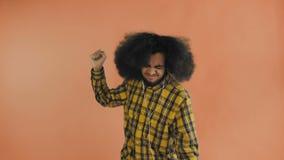 Uomo afroamericano positivo facendo uso del telefono a musica d'ascolto in sue cuffie su fondo arancio Concetto delle emozioni stock footage