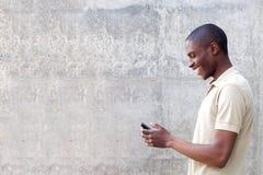 Uomo afroamericano sorridente che cammina e che esamina cellulare Fotografia Stock Libera da Diritti