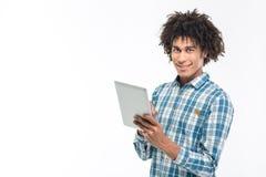 Uomo afroamericano sorridente che per mezzo del computer della compressa Fotografie Stock