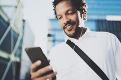 Uomo afroamericano sorridente in cuffia che rende video chiamata tramite smartphone disponibila Concetto del tipo che usando Inte Immagini Stock Libere da Diritti