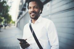 Uomo afroamericano sorridente in cuffie che distoglie lo sguardo e che ascolta le canzoni sul suo telefono cellulare Priorità bas Immagini Stock Libere da Diritti