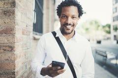 Uomo afroamericano sorridente in cuffie che guardano alla macchina fotografica e che ascoltano le canzoni sul suo telefono cellul Fotografie Stock Libere da Diritti
