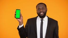 Uomo afroamericano sorridente in formalwear che mostra telefono prekeyed, pubblicità video d archivio