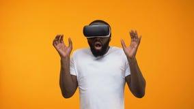 Uomo afroamericano spaventato facendo uso della cuffia avricolare di realtà virtuale, simulazione, primo piano stock footage