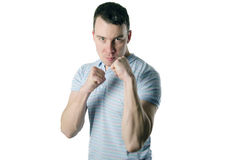 Uomo aggressivo che mostra i suoi pugni su un fondo bianco Fotografie Stock Libere da Diritti