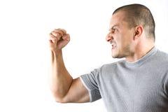 Uomo aggressivo che mostra il suo pugno isolato su bianco Fotografie Stock Libere da Diritti