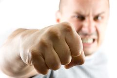 Uomo aggressivo che mostra il suo pugno isolato su bianco Immagine Stock