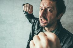 Uomo aggressivo che perfora con il pugno, ` s POV della vittima fotografia stock