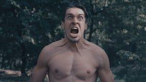 Uomo aggressivo con un torso nudo furioso che grida nella foresta stock footage