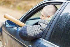 Uomo aggressivo con una mazza da baseball in automobile immagine stock