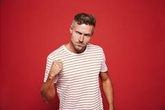 Uomo aggressivo in maglietta a strisce che guarda con l'avversione e la manifestazione fotografie stock