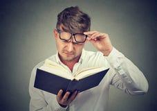 Uomo aggrottante le sopracciglia che ha problemi con lettura Fotografia Stock Libera da Diritti