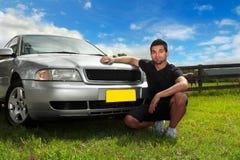 Uomo al lato dell'automobile in sole di pomeriggio Fotografia Stock