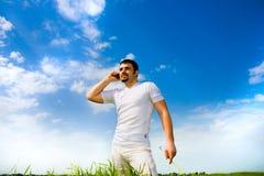 Uomo al telefono nel campo sotto cielo blu Immagine Stock