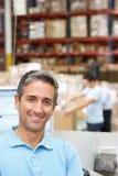 Uomo al terminale di calcolatore elettronico nel magazzino di distribuzione Immagini Stock