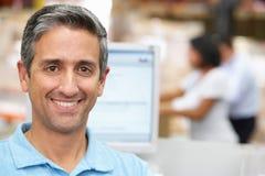 Uomo al terminale di calcolatore elettronico nel magazzino di distribuzione Fotografie Stock