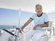 Uomo al timone dell'yacht di lusso Immagini Stock Libere da Diritti