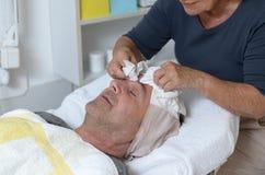 Uomo al trattamento facciale di ricezione concentrare di bellezza Fotografie Stock