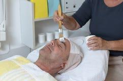 Uomo al trattamento facciale di ricezione concentrare di bellezza Fotografia Stock