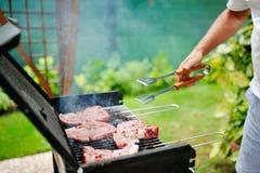 Uomo alla griglia del barbecue che prepara carne per un ricevimento all'aperto Immagini Stock