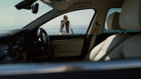 Uomo alla moda che fuma sui precedenti dell'oceano, tiri tramite l'automobile della carrozza archivi video