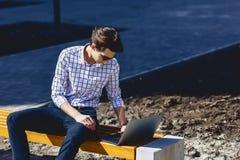 uomo alla moda che lavora al computer portatile alla via Fotografia Stock