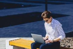 uomo alla moda che lavora al computer portatile alla via Immagine Stock